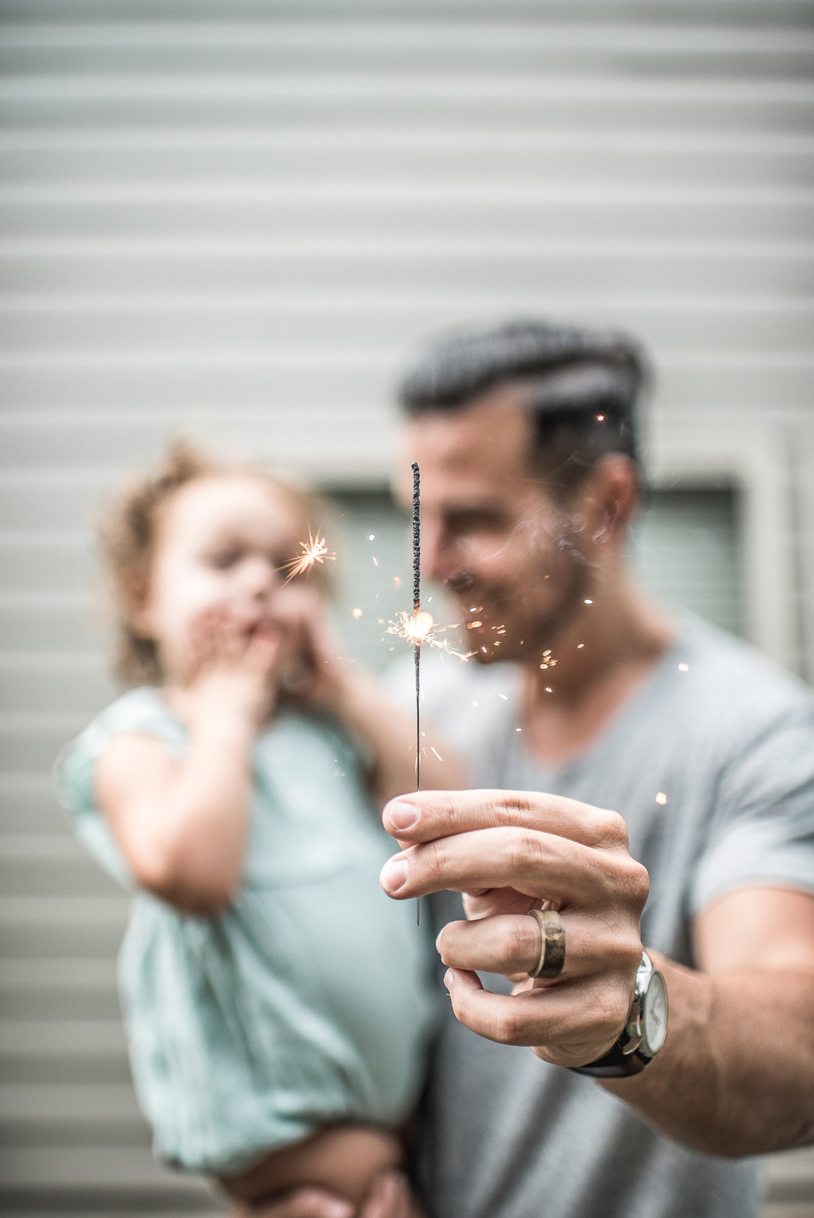 man holding sparkler and child - best neighborhoods in katy texas - most popular neighborhoods in katy texas